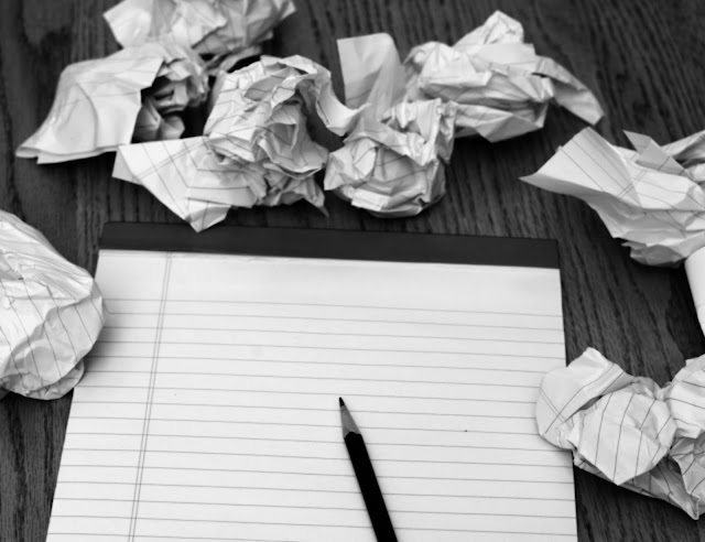 Writer's Block - blank paper with pencil and crumpled up paper scattered around