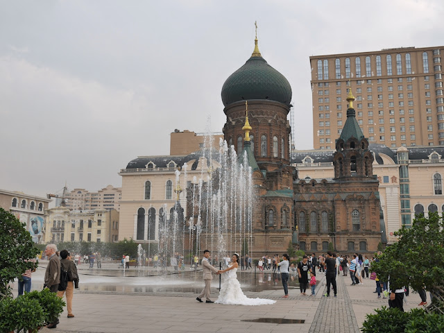 couple taking wedding photos next to the Saint Sophia Cathedral in Harbin