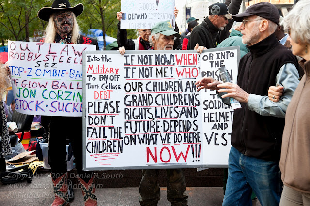 a photo of occupy wall street demonstrators holding signs at zuccatti park in new york
