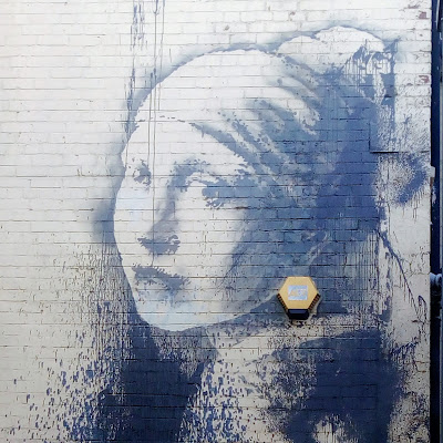 Banksy artwork, featuring a woman in the style of the girl with the pearl earring.
