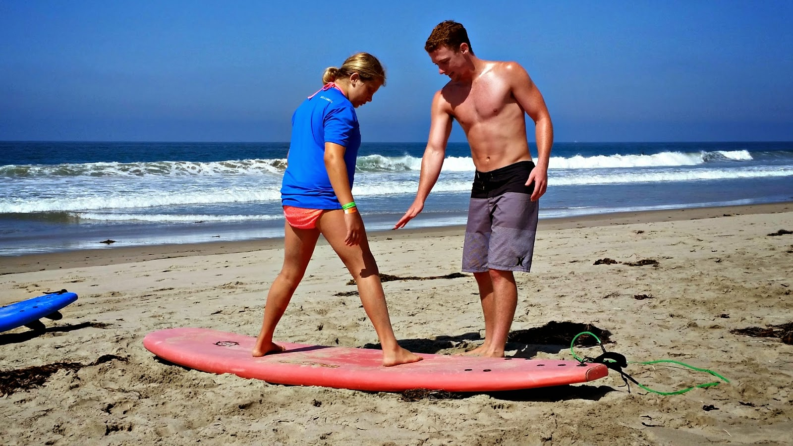 Camp counselor giving female camper a surfing lesson on the beach in Malibu