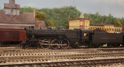 black steam locomotive (model) with tracks and miniature buildings