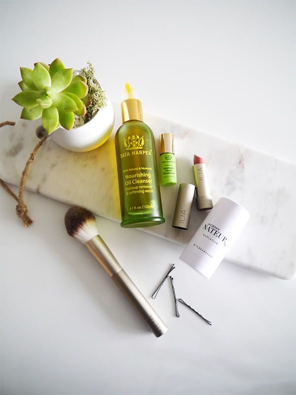 Flatlay featuring succulent, a couple of bobby pins, marble cheese board, Tata Harper Nourishing Oil Cleanser, ILIA lipstick and brush, Tata Harper Aromatic Stress Treatment, Agent Nateur natural deodorant