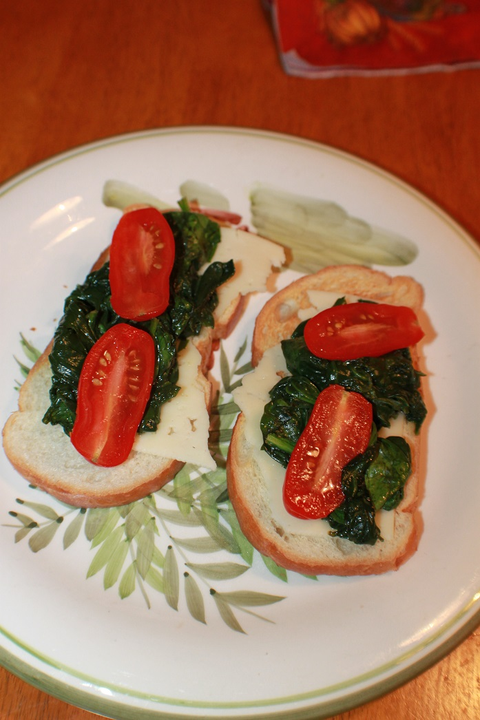 This is toasted Italian bread with cheese, spinach and tomatoes on the palm tree plate