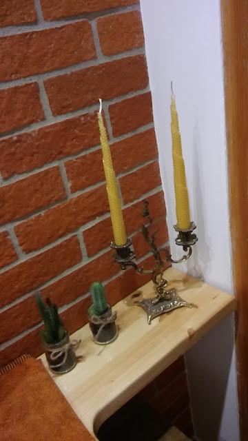 mosiężny świecznik na tle ściany z cegły