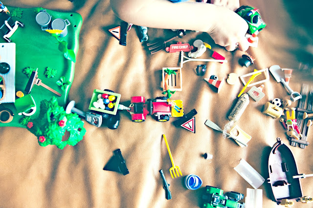 A child's hand playing with small toys.