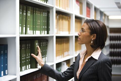 Woman searching for book on bookshelf