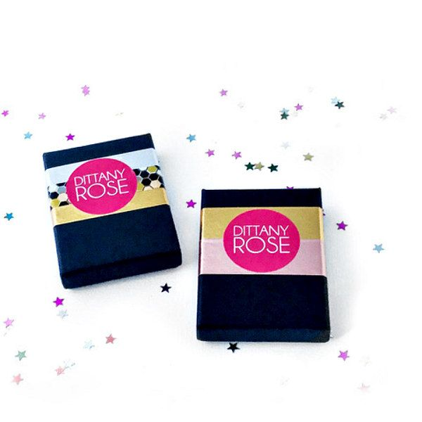 Black boxes with hot pink stickers are packaging examples from Dittany Rose paper jewellery