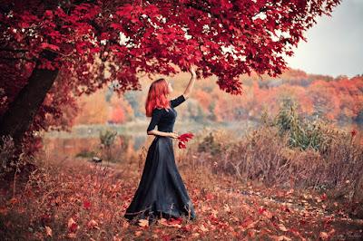 Chica pelirroja con hojas rojas y fondo de arboles