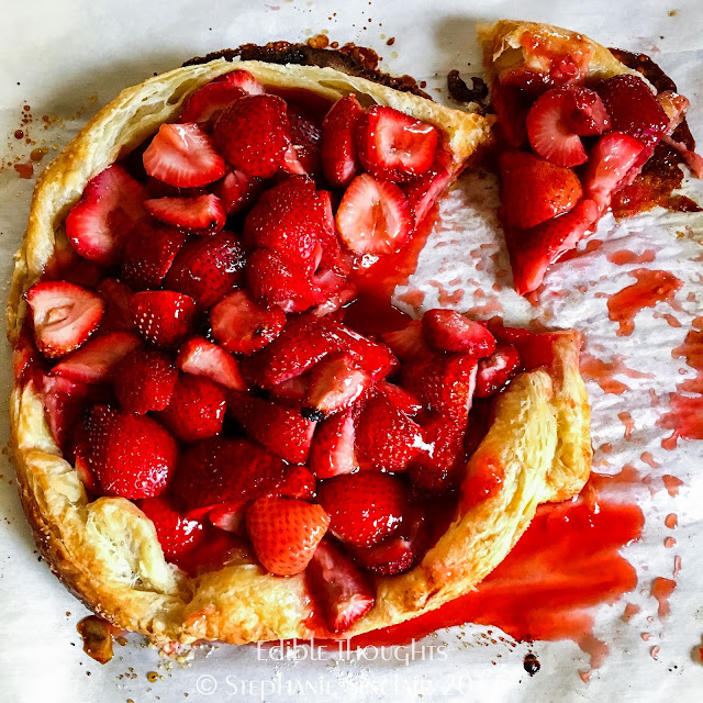 Image from above at a cut baked free form puff pastry pie with ooey gooey strawberries.