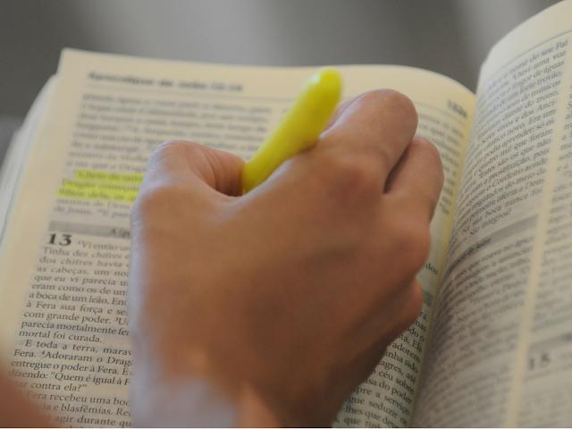 Pessoa lendo a bíblia e usando um marcador de texto