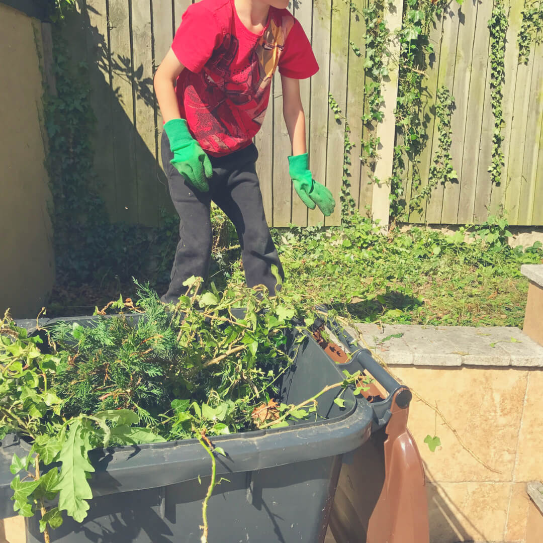 A young boy wears green garden gloves as he attempts to pick up weeds from the garden. Here's how to teach your children about work.