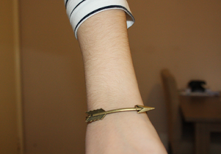 close up of a gold brass arrow bracelet