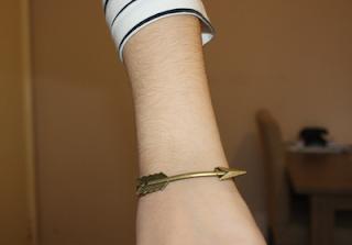 close up of a gold brass arrow bracelet