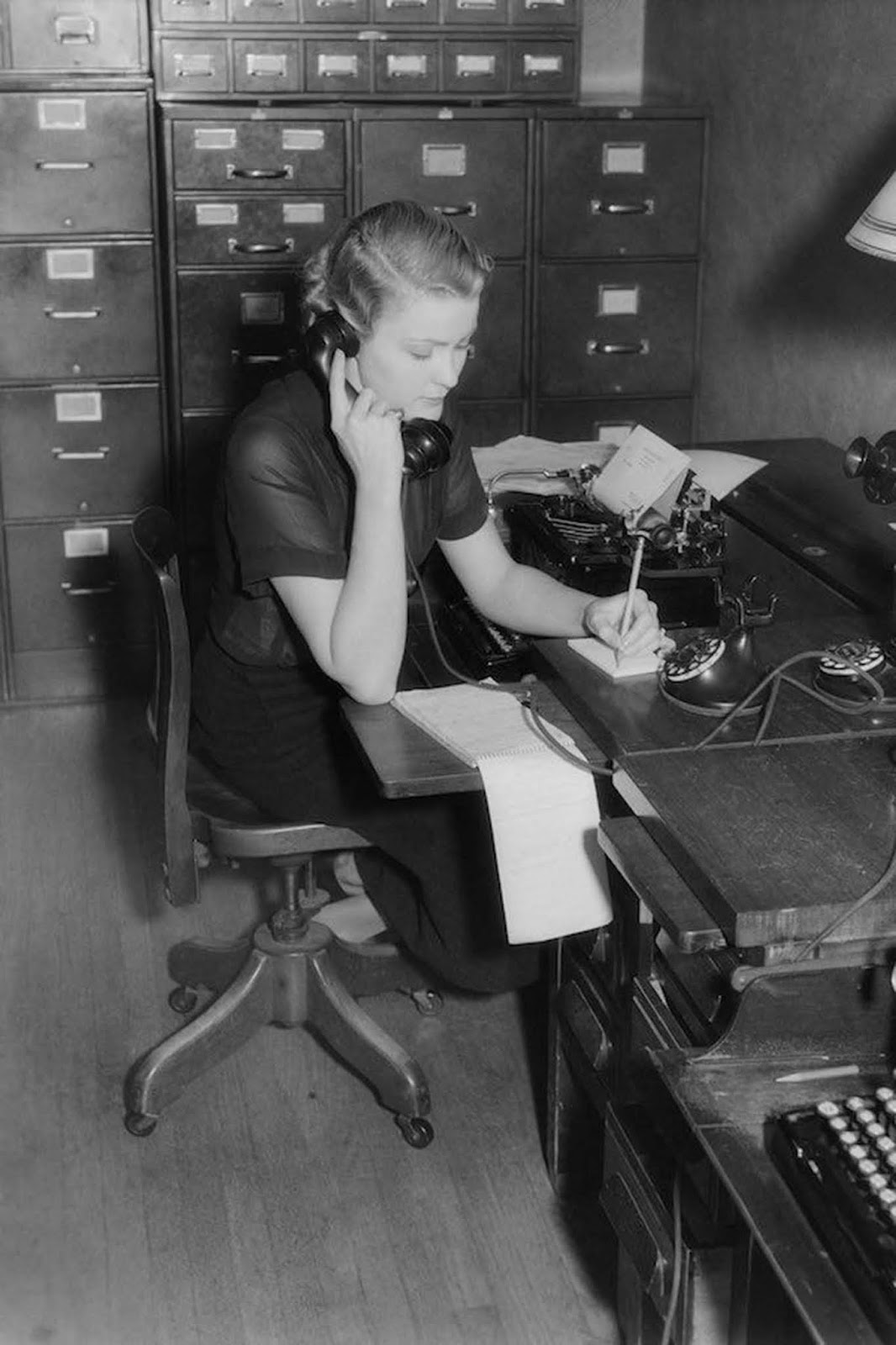 An American secretary sits at a desk behind a typewriter, on the phone taking messages. She wears black, and her blouse is semi-sheer. Her hair is worn neck-length with a permanent wave. 1930.