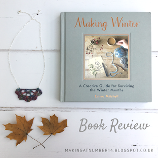 Flat lay of a Making Winter book, necklace and preserved leaves