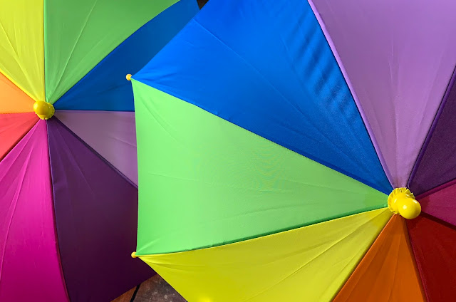 Two open rainbow umbrellas
