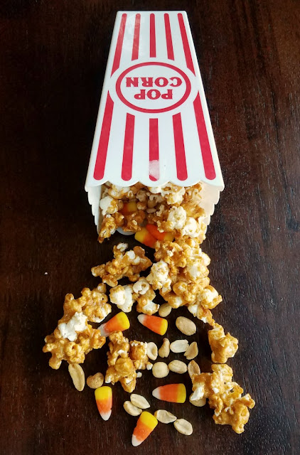 peanut butter popcorn, peanuts and candy corn spilling out of popcorn container