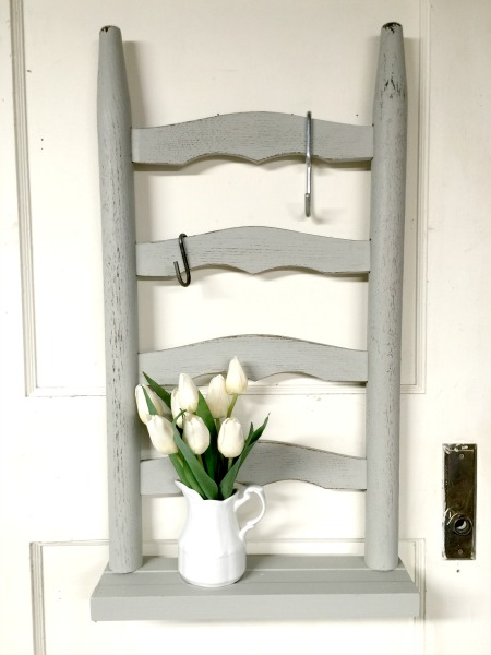 Grey ladder back chair shelf with pitcher of flowers