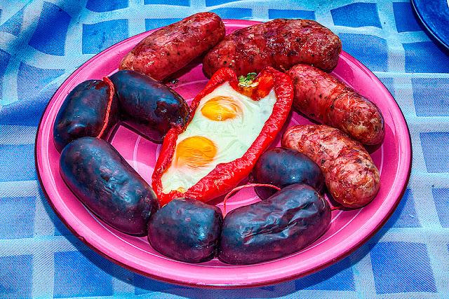 Plato con morcillas, chorizos y dos huevos fritos en pimiento rojo