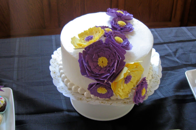 This is a cake decorated with paper peony flowers.