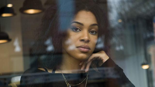 mujer mulata con una expresión de tristeza mirando por la ventana