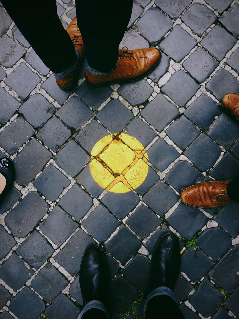 O mundo é bom, sapatos na calçada com pintura amarela