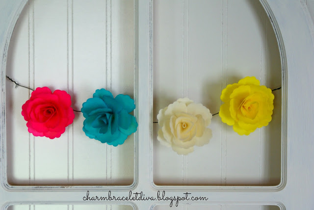 Brightly colored paper flowers hanging from farmhouse window frame