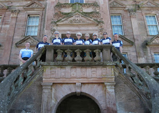 Seven smiling cyclists and two guides on the front steps of Drumlanrig Castle, Scotland