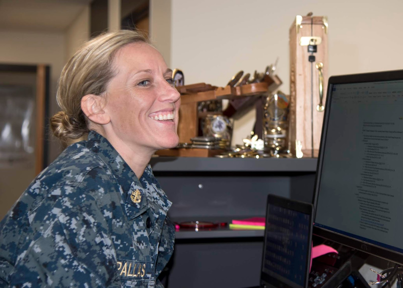 A female in a U.S. Navy uniform is at her desk working. She's laughing and looking toward her computer.
