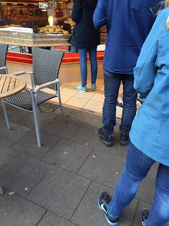 Anstehen zum Sonntagsbrötchenkauf: Viele Menschen, Theke, Verkäuferin, Brötchen, Stuhl, Tisch, Hunger