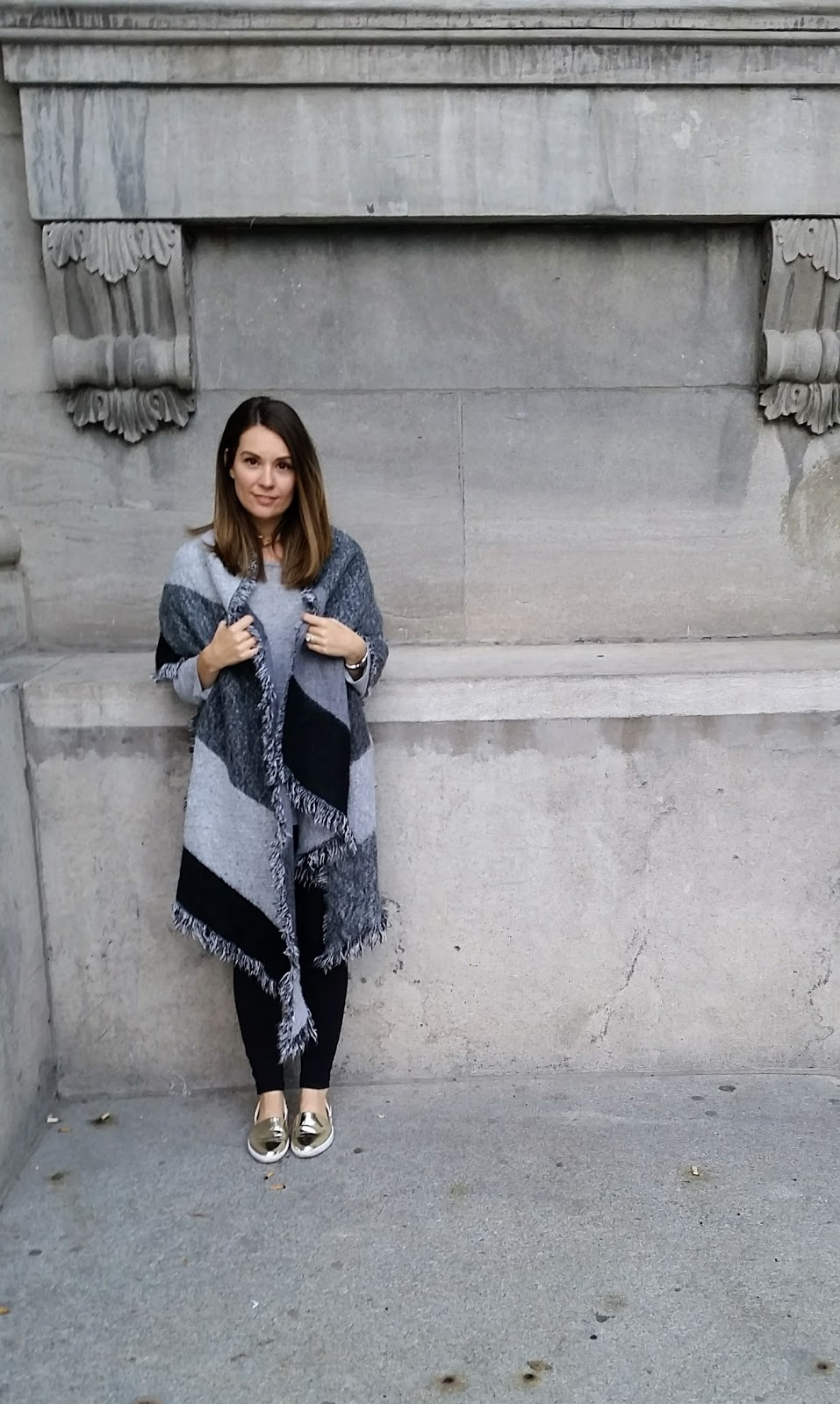 Oversize grey scarf, grey sweater, black leggings, gold flats