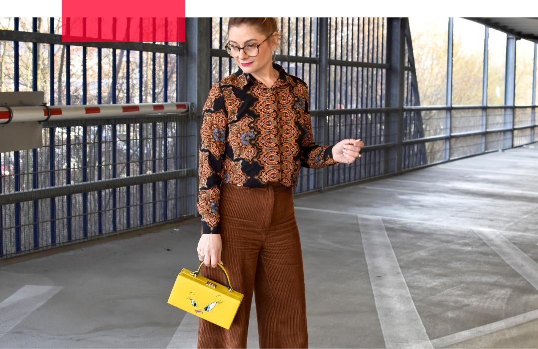 Frau trägt Cordhose in Hellbraun. Braune Bluse mit Blumenmuster, gelbe Handtasche, weiße Stiefel,