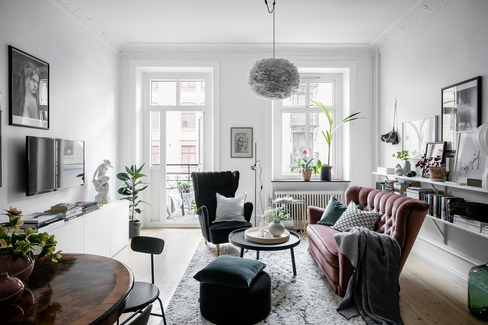 small  scandinavian apartment with  gray kitchen, white floors, pink sofa