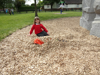 boy buried under pile of woodchips