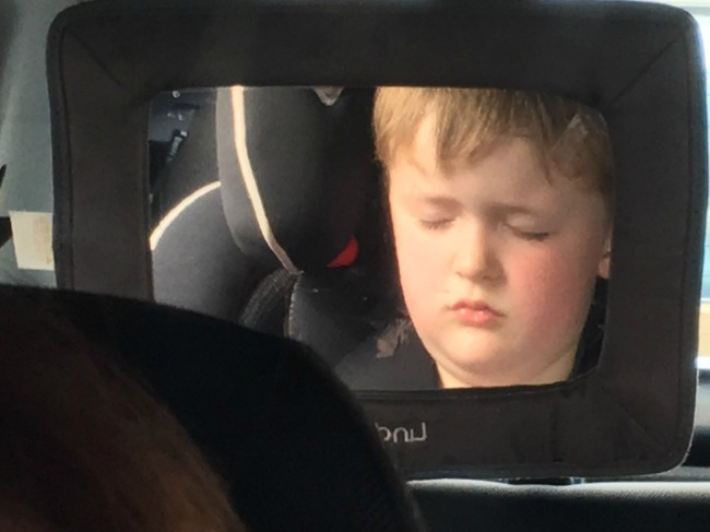 reflection-in-mirror-of-boy-asleep-in-car