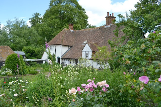 A view of Manor Farm farmhouse though a flower garden