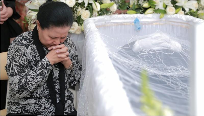 Amin Yudhayani berdoa di samping peti jenazah Mike Mohede