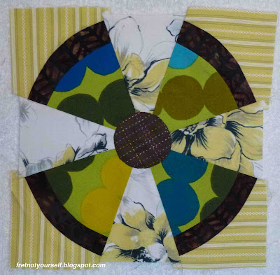 Marimekko fabric in greens and blues is used with browns and yellows to create a Steam Punk block.
