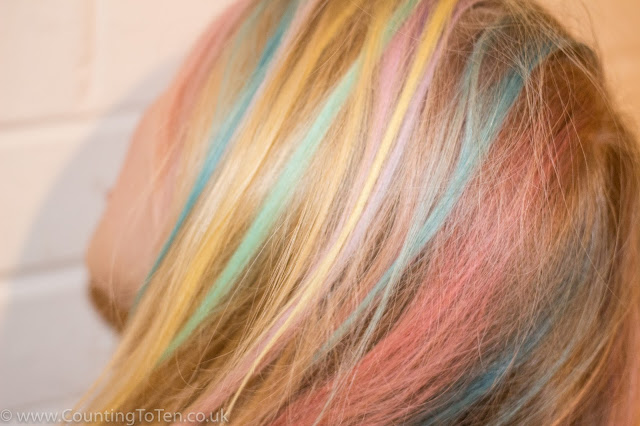 A view of the side of my daughter's blonde hair with streaks of different colours in it