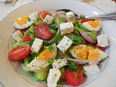 na talerzu: czerwone pomidory, pokrojone ogórki, jajko, kawałki fety, krążki cebuli, grecka sałatka