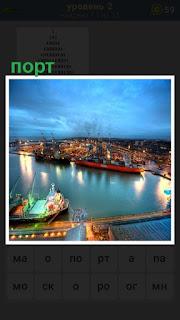 Панорама порта в котором горят огни и идет работа около судов стоящих