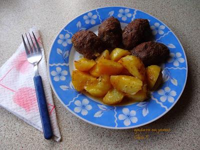 Γαλαζιο πιατο με ασπρα λουλουδια μπορντουρα με περιεχομενο πατατες φούρνου και κεφτέδες διπλα υπαρχει πηρουνι με γαλαζια λαβη