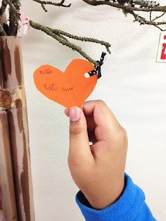 Mão de aluno a colocar um coração de papel cor de laranja com o seguinte agradecimento: estar vivo