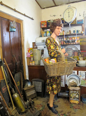 Full-scale model of the interior of a 1930s shop, with a customer with a basket on her arm.