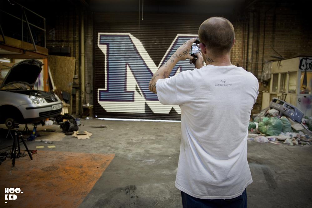UK street artist Ben Eine stood in front of one of his typographic shutters
