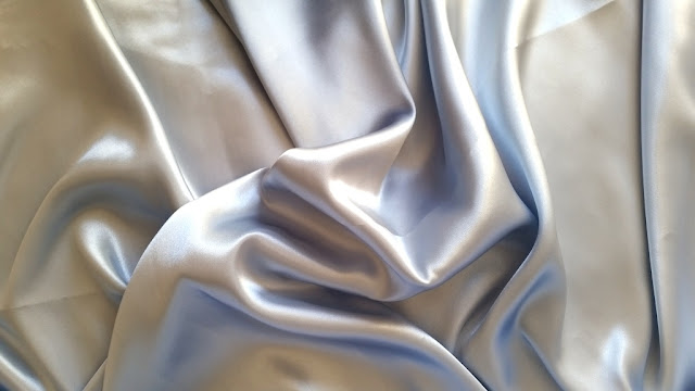 A swathe of shiny pastel blue satin. The deep shadows show traces of the blue. The shininess reflects light and makes the fabric look cooler and lighter in the photograph than it actually is. It is a pastel, cool, grey blue.