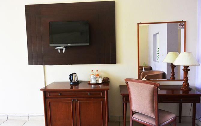 Fasilitas di kamar seperti televisi dan rak pakaian