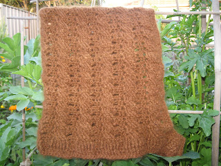 Right hand side of alpaca cabled hood. It is hanging in the garden.