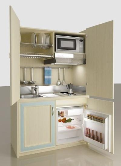 desain dapur dalam lemari yang feminin, dengan kombinasi warna beige dan sedikit biru pastel. rak piring yang dipasang tepat di atas bak cuci piring. Disediakan juga gantungan spatula dan lap. Ukuran kulkasnya, cukup untuk orang yang tinggal sendiri.